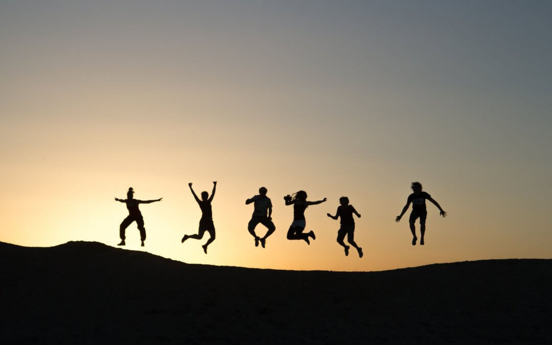 Silhouettes of people jumping against sunset